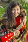 El adolescente toca la guitarra mientras que se sienta al aire libre Fotografía de archivo libre de regalías