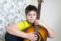 El adolescente toca una guitarra acústica Foto de archivo libre de regalías