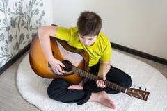 El adolescente toca una guitarra acústica Imagen de archivo libre de regalías
