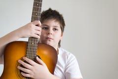 El adolescente toca una guitarra acústica Foto de archivo