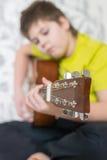 El adolescente toca una guitarra acústica Imágenes de archivo libres de regalías