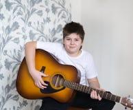 El adolescente toca una guitarra acústica Fotografía de archivo libre de regalías