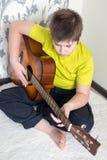 El adolescente toca una guitarra acústica Fotos de archivo