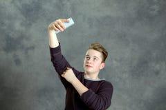 El adolescente toma un autorretrato con el teléfono Fotografía de archivo