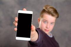 El adolescente toma un autorretrato con el teléfono Imagen de archivo