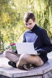 El adolescente trabaja detrás de un ordenador portátil Fotos de archivo libres de regalías
