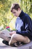 El adolescente trabaja detrás de un ordenador portátil Fotografía de archivo libre de regalías