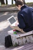 El adolescente trabaja detrás de un ordenador portátil Foto de archivo libre de regalías
