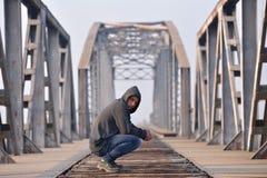 El adolescente triste del pensador en la sentada de la depresión se agachó en el bridg Foto de archivo libre de regalías