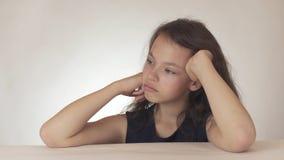 El adolescente triste hermoso expresa el resentimiento y la tristeza en el fondo blanco Imagen de archivo