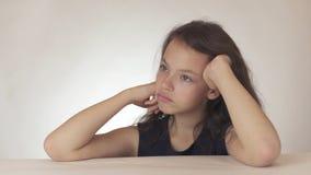 El adolescente triste hermoso expresa el resentimiento y la tristeza en el fondo blanco Imagenes de archivo