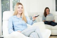 El adolescente ve la TV mientras que la madre trabaja en el ordenador portátil Imagen de archivo