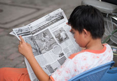 El adolescente vietnamita lee el periódico sobre fútbol Fotos de archivo libres de regalías