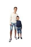 El adolescente y el niño pequeño altos se colocan juntos de abarcamiento Fotografía de archivo libre de regalías