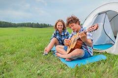 El adolescente y la muchacha cerca de la tienda tocan la guitarra Imágenes de archivo libres de regalías