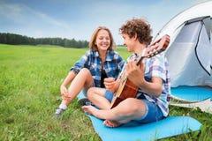 El adolescente y la muchacha cerca de la tienda tocan la guitarra Imagen de archivo
