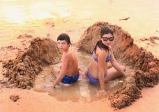El adolescente y la muchacha juegan con la arena en la playa Imágenes de archivo libres de regalías