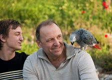 El adolescente y su papá con un loro gris Jaco. Imagen de archivo