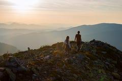 El adolescente y un individuo están caminando a lo largo de un canto pedregoso Foto de archivo libre de regalías