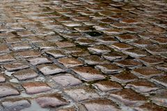 El adoquín mojado empedró el camino después de una tormenta de la lluvia Foto de archivo