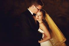 El adorno del novio y de la novia elegantes de la moda está abrazando en la parte posterior Foto de archivo