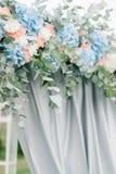 El adorno hecho de hortensias del rosa en colores pastel y del azul cuelga sobre weddi Imágenes de archivo libres de regalías