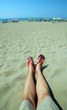 El adulto con las piernas y las chancletas largas en el pie descansa sobre el san Fotografía de archivo libre de regalías
