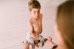 El adulto da a niño una pesa de gimnasia Fotos de archivo libres de regalías