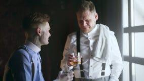 El adulto dos tattoed el whisky de las bebidas de los amigos y tiene una charla, estilo de la mafia de los años 30, barra de los  almacen de metraje de vídeo