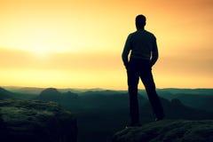 El adulto en pantalones negros, chaqueta se sienta en el borde del acantilado Imagen de archivo libre de regalías