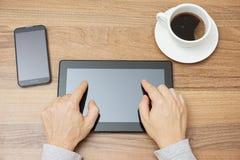 El adulto joven está mecanografiando con dos fingeres en la tableta, v superior Imagen de archivo libre de regalías