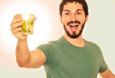 El adulto joven está sosteniendo un vidrio de la bebida hecho del limón Fotografía de archivo
