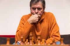 El adulto mayor está jugando a ajedrez imagen de archivo