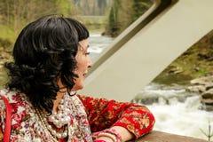 El adulto vistió elegante miradas de la mujer abajo en un río de la montaña Bl Fotos de archivo
