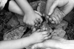El adulto y chilcren el círculo de piedra de las manos de la explotación agrícola Imagen de archivo