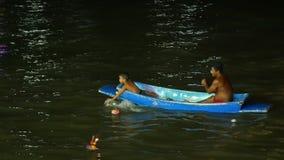 El adulto y el niño de la gente son canotaje que busca el krathong en la moneda del hallazgo del río o el dinero y ellos guardan