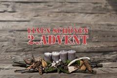 El advenimiento de la decoración de la Feliz Navidad que quemaba la vela gris empañó al alemán 2do del mensaje de texto del fondo Imagenes de archivo