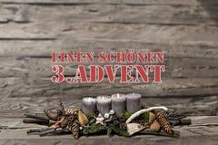 El advenimiento de la decoración de la Feliz Navidad que quemaba la vela gris empañó al alemán 3ro del mensaje de texto del fondo Fotografía de archivo libre de regalías