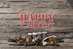 El advenimiento de la decoración de la Feliz Navidad que quemaba la vela gris empañó el englisch 2do del mensaje de texto del fon Fotografía de archivo