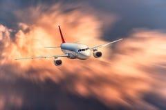 El aeroplano con efecto de la falta de definición de movimiento está volando en nubes anaranjadas grandes en la puesta del sol Ae imágenes de archivo libres de regalías