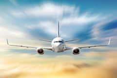 El aeroplano con efecto de la falta de definición de movimiento está volando en nubes anaranjadas en la puesta del sol Transporte foto de archivo