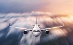 El aeroplano con efecto de la falta de definici?n de movimiento est? volando sobre las nubes en la puesta del sol fotos de archivo