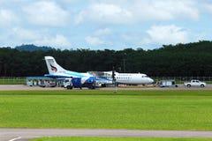 El aeroplano del ATR 72-600 en pista del taxi del aeropuerto con las hierbas coloca Imagen de archivo