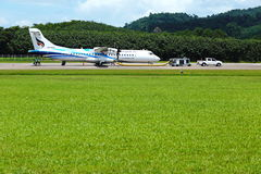 El aeroplano del ATR 72-600 en pista del taxi del aeropuerto con las hierbas coloca Foto de archivo libre de regalías