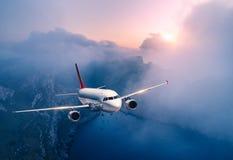 El aeroplano del pasajero est? volando sobre las nubes en la puesta del sol fotos de archivo