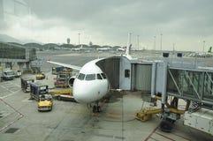 El aeroplano en la pista de despeque Hong Kong International Airport es el aeropuerto comercial que sirve a Hong Kong foto de archivo libre de regalías