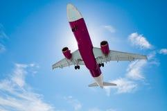 El aeroplano está aterrizando en el aeropuerto con el cielo azul Imagenes de archivo