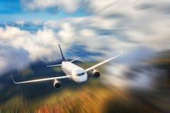El aeroplano moderno con efecto de la falta de definición de movimiento está volando en nubes bajas en la puesta del sol Aeroplan imagen de archivo