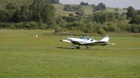 El aeroplano propulsor-conducido de asiento doble blanco del crucero PS-28 saca en pista de aterrizaje de la hierba en el co almacen de metraje de vídeo