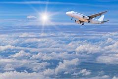 El aeroplano que se va volando adentro al cielo sobre el blanco se nubla con luz del sol Imagenes de archivo